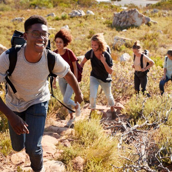 Millennial African American man leading friends hiking single file uphill on a path in countryside